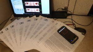 La foto mostra il client Windows di redEyes, uno smartphone con redEyes in esecuzione e vari documenti cartacei
